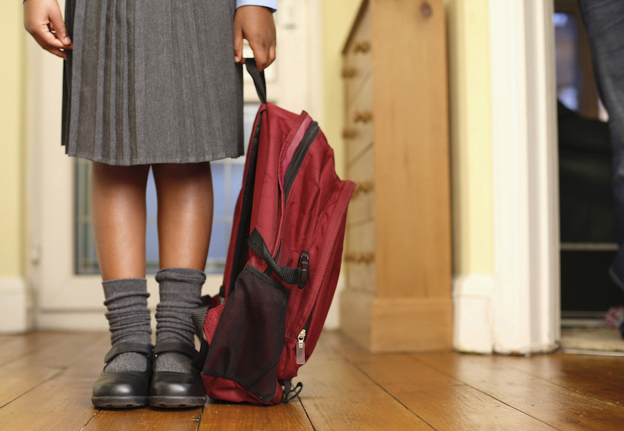 Lower half of a young girl's body, wearing a school uniform skirt, knee socks and black shoes, and holding a red backpack in her left hand